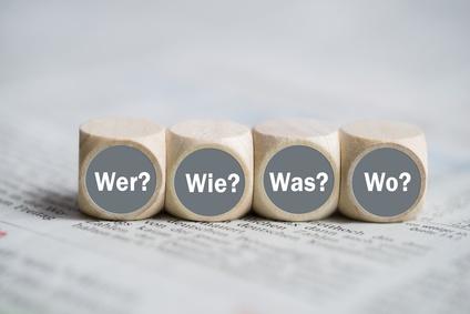 """Wrfel mit den Wrtern """"Wer, Wie, Was und Wo"""" auf einer Zeitung"""