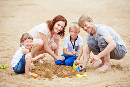 Glückliche Familie spielt im Familienurlaub am Strand im Sommer