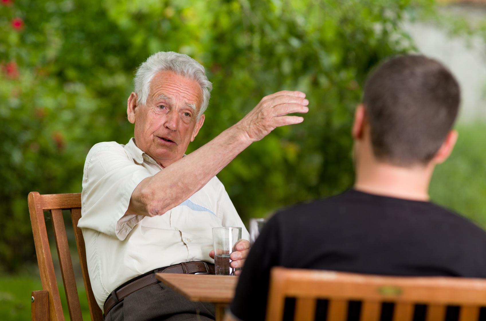 Serious old man talking with grandson and explaining by hand